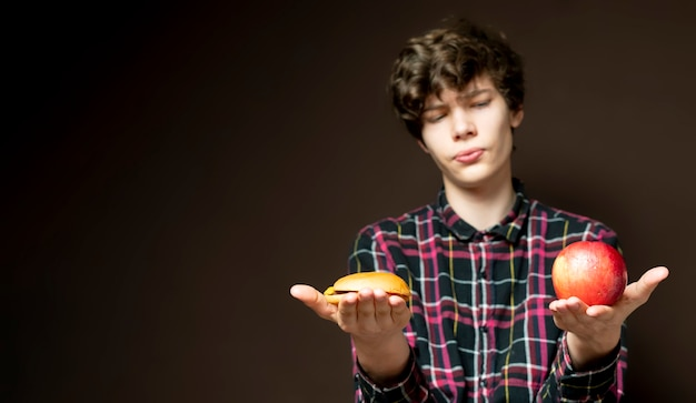 Young male holding and choosing between apple or hamburger b