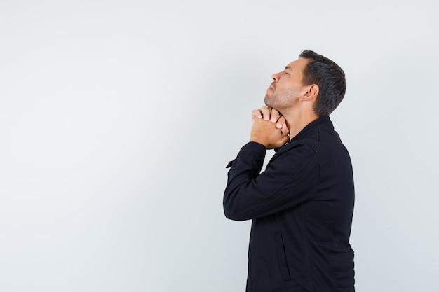 Giovane maschio che tiene le mani giunte nel gesto di preghiera in giacca nera e sembra speranzoso.