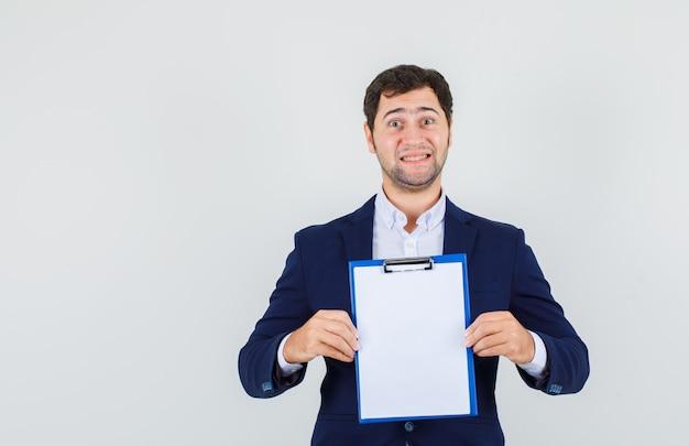 Молодой мужчина держит буфер обмена в костюме и выглядит веселым, вид спереди.