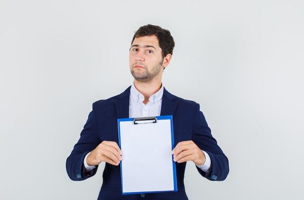 スーツにクリップボードを保持し、厳格に見える若い男性。正面図。