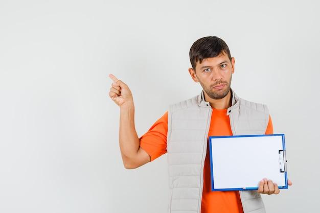 クリップボード、鉛筆、tシャツ、ジャケットの正面図で左上を指している若い男性。