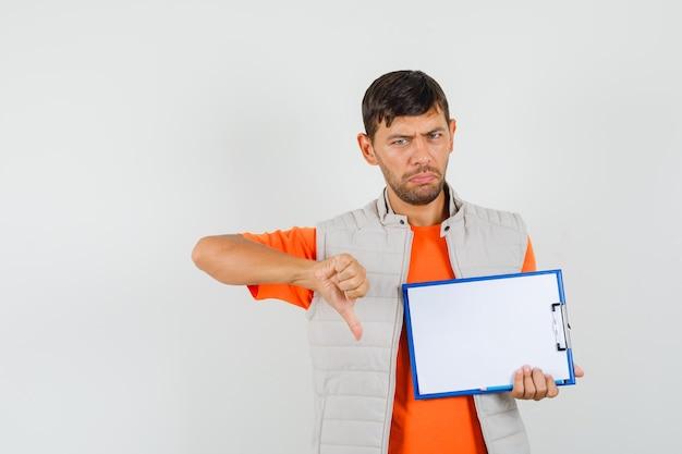クリップボード、鉛筆を保持している若い男性、tシャツ、ジャケットで親指を下に見せて、動揺して、正面図。