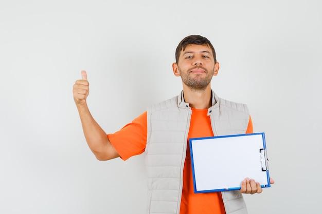 クリップボード、鉛筆を保持している若い男性、tシャツ、ジャケット、陽気な顔をして親指を表示、正面図。