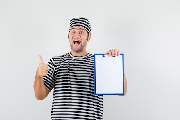 Giovane maschio che tiene appunti, mostrando il pollice in su in t-shirt, cappello e guardando allegro, vista frontale.