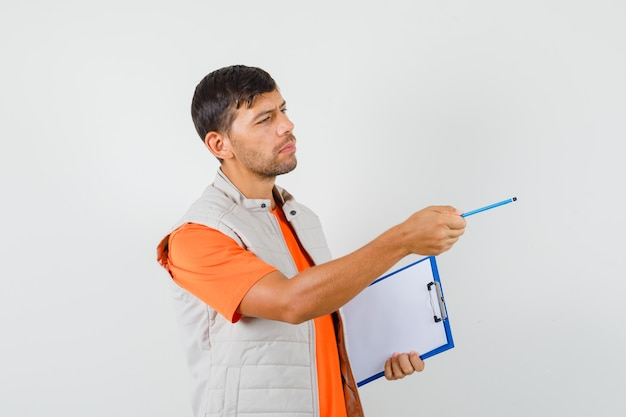 Young male holding clipboard while pointing away in t-shirt, jacket and looking concerned , front view.