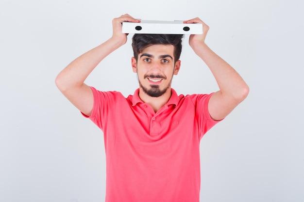 젊은 남성 지주 t- 셔츠에 머리 위에 피자 상자를 폐쇄 하 고 쾌활 한, 전면보기를 찾고.