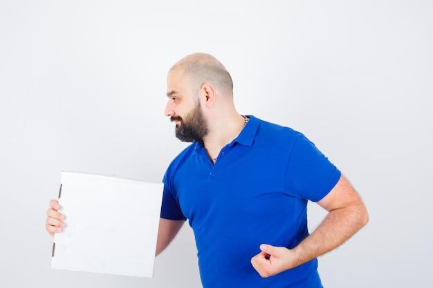 닫힌 피자 상자를 들고 있는 젊은 남성은 티셔츠를 입고 행복해 보이는 앞모습을 바라보고 있습니다.