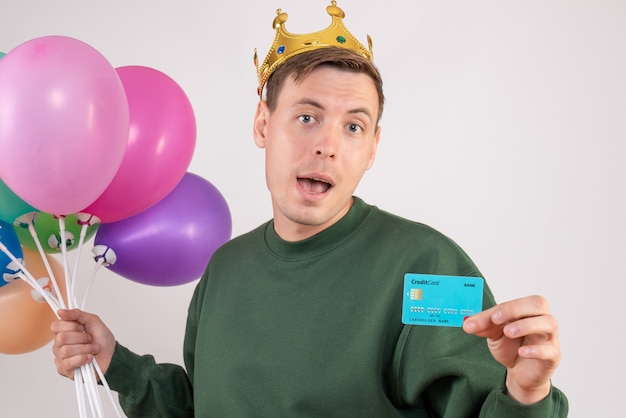 Young male holding colorful balloons and bank card on white