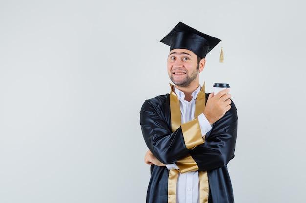 대학원 유니폼에 커피 한잔 들고 기쁜 찾고 젊은 남성. 전면보기.