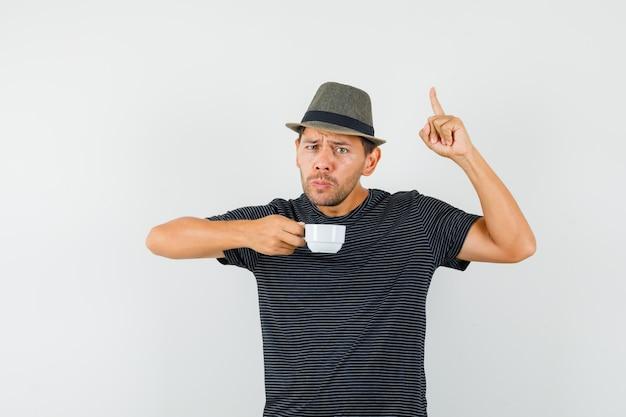 Молодой мужчина держит чашку напитка, указывая вверх в шляпе футболки