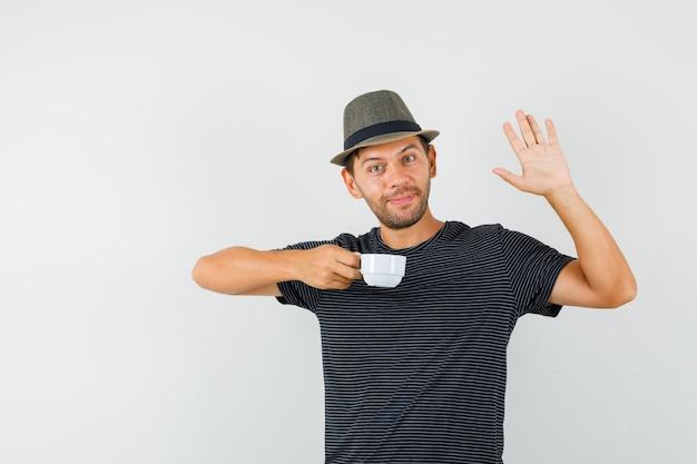 Молодой мужчина держит чашку напитка, машет рукой в шляпе футболки и выглядит весело