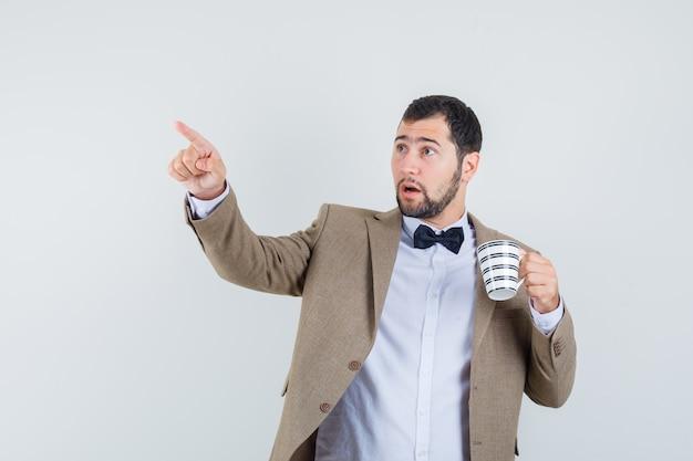 Молодой мужчина держит чашку напитка, указывая прочь в костюме и глядя сосредоточенно, вид спереди.
