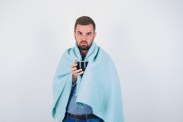シャツ、ジーンズ、毛布でカメラを見て、真剣に見ながらカップを保持している若い男性。正面図。