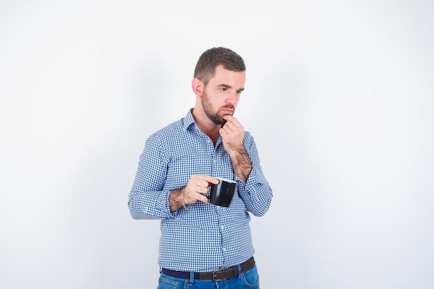 シャツ、ジーンズで目をそらし、思慮深く、正面図を見ながらカップを保持している若い男性。