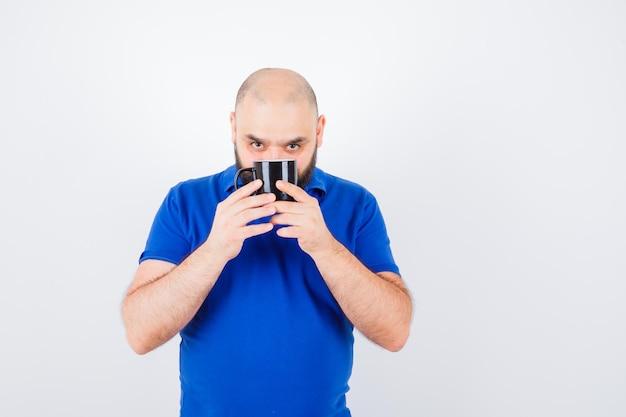 Giovane maschio che tiene tazza mentre guarda la macchina fotografica in camicia blu e sembra concentrato, vista frontale.