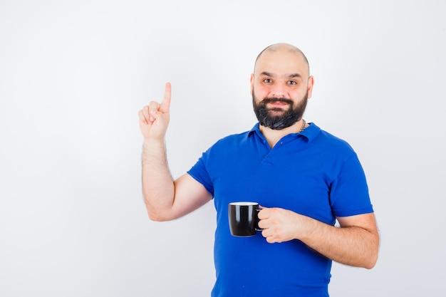 青いシャツ、正面図で上向きしながらカップを保持している若い男性。