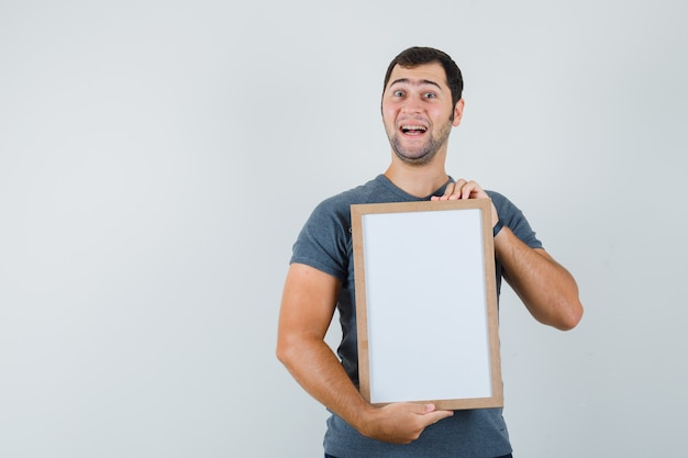 Young male holding empty frame in grey t-shirt and looking happy