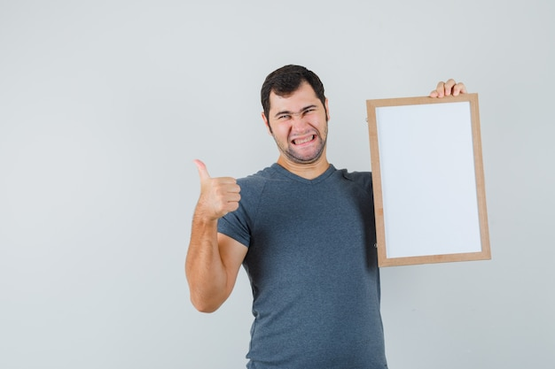 Young male holding empty frame showing thumb up in grey t-shirt and looking cheerful