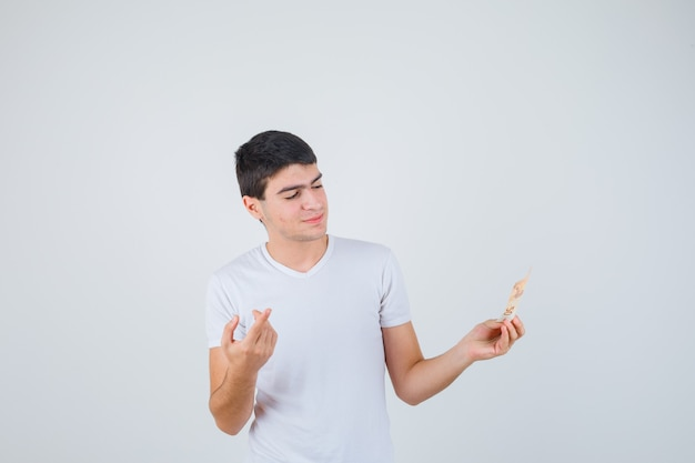 Молодой мужчина держит евробанкнот, указывая вверх в футболке и выглядит веселым. передний план.