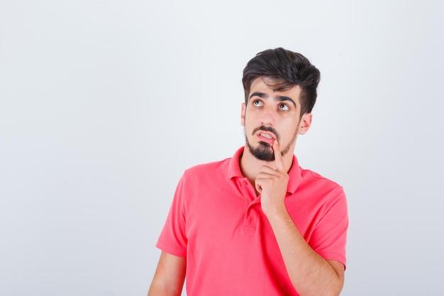Giovane maschio che tiene il dito sul mento in maglietta rosa e sembra pensieroso, vista frontale.