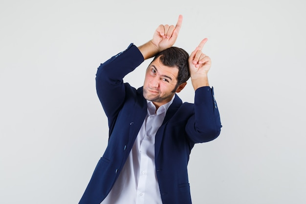 Young male holding fingers over head as bull horns in shirt