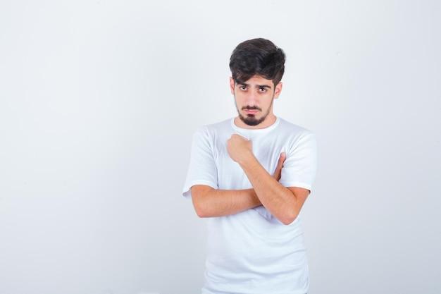 Giovane maschio che tiene il pugno sul petto in maglietta e sembra fiducioso, vista frontale.