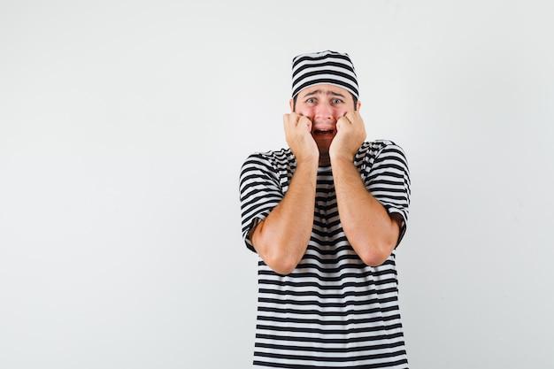 Tシャツ、帽子、不安そうな正面図で頬に拳を持っている若い男性。