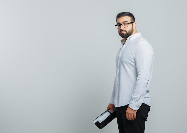 흰 셔츠, 바지에 폴더를 들고 자신감을 찾고 젊은 남성