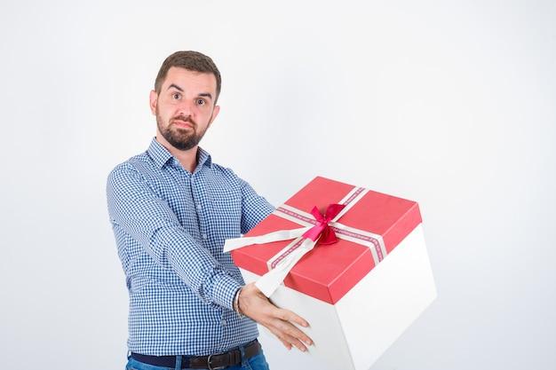 Молодой мужчина держит подарочную коробку в рубашке и недоумевает. передний план.