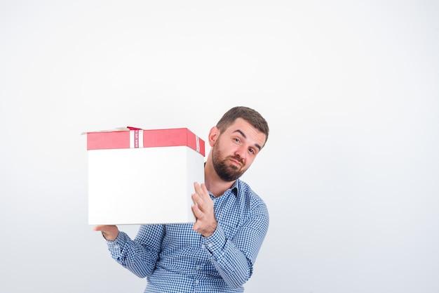 Молодой мужчина держит подарочную коробку в рубашке, джинсах и нерешительно смотрит, вид спереди.