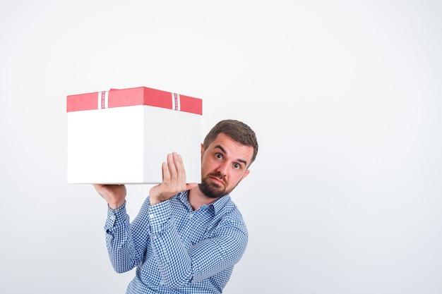 Молодой мужчина держит подарочную коробку в рубашке, джинсах и выглядит озадаченным. передний план.