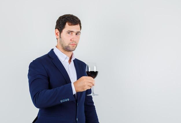 スーツにアルコール飲料のガラスを保持し、落ち着いて見える若い男性。正面図。
