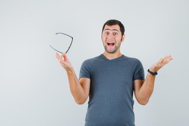 Молодой мужчина держит очки в серой футболке и выглядит веселым
