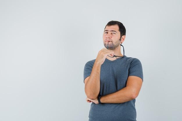 Молодой мужчина держит очки в серой футболке и выглядит задумчивым