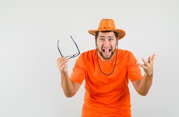 オレンジ色のtシャツ、帽子で叫び、興奮しているように見えながら眼鏡を保持している若い男性。正面図。