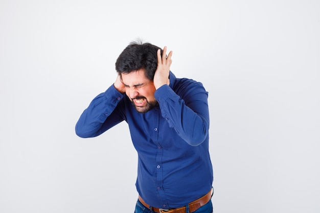 Young male holding hand on ears while shouting in royal blue shirt and looking angry. front view.