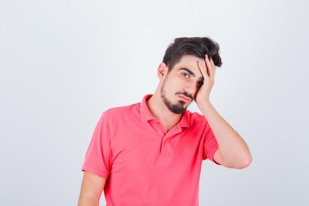 Giovane maschio che tiene la mano sul viso in maglietta rosa e sembra pensieroso. vista frontale.