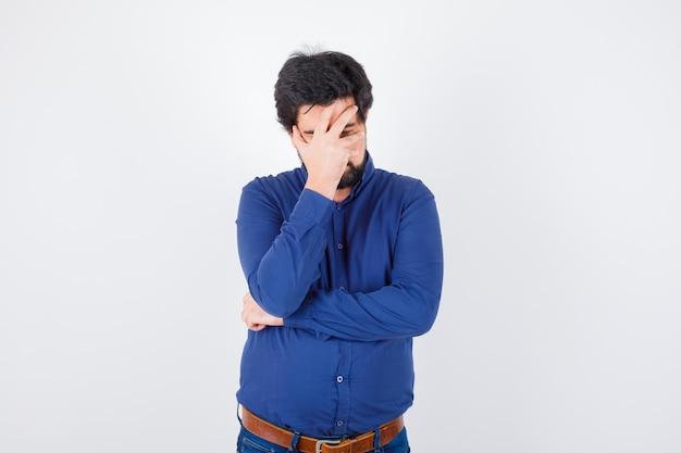 Giovane maschio che tiene la mano sul viso in camicia blu reale e sembra stressante, vista frontale.