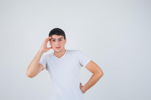 Giovane maschio tenendo la mano sopra la testa in t-shirt e guardando concentrato, vista frontale.