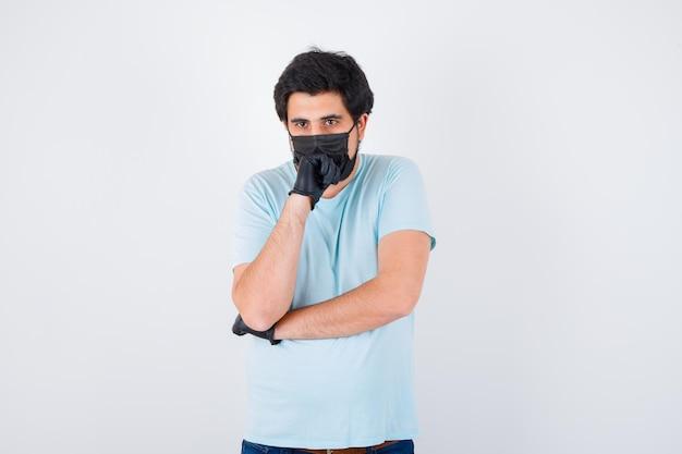 Giovane maschio che tiene la mano sulla bocca in maglietta e sembra esitante. vista frontale.