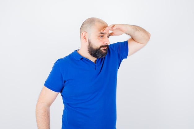 Tシャツで額に手を握って、不思議に見える、正面図の若い男性。