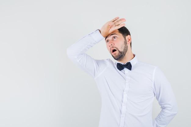白いシャツを着て額に手を握り、後悔している若い男性。正面図。