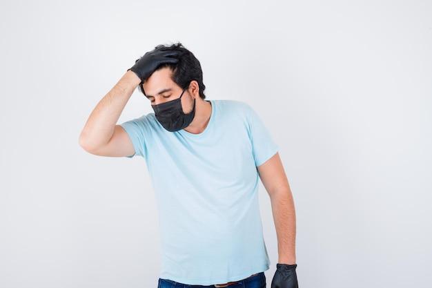 Молодой мужчина держит руку на голове в футболке и выглядит нездоровым, вид спереди.