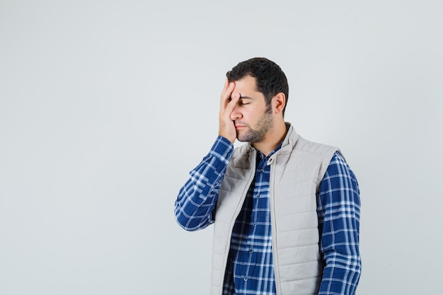 シャツ、ノースリーブのジャケット、疲れた顔、正面図で彼の顔に手をつないでいる若い男性。テキスト用のスペース
