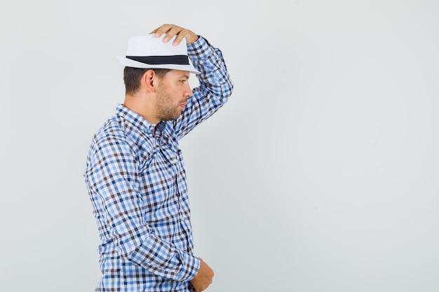 チェックのシャツで彼の帽子に手をつないでいる若い男性