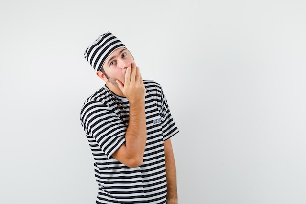 젊은 남성 t- 셔츠, 모자에 입에 손을 잡고 놀 찾고, 전면보기.