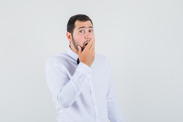 白いシャツを着て口に手をつないで、驚いたように見える若い男性、正面図。
