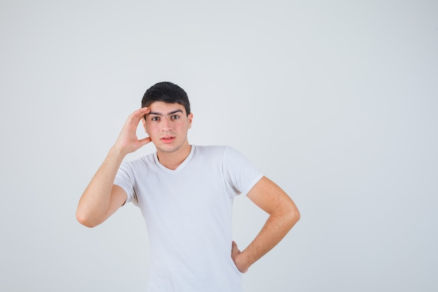 젊은 남성 t- 셔츠에 머리 위로 손을 잡고 초점, 전면보기를 찾고.