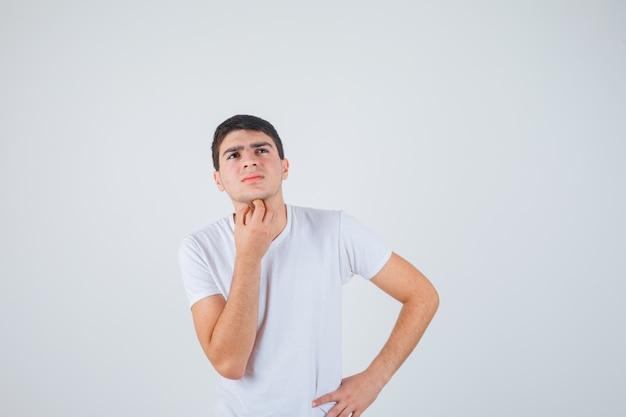 T- 셔츠에 턱 아래 손을 잡고 사려 깊은, 전면보기를 찾고 젊은 남성.
