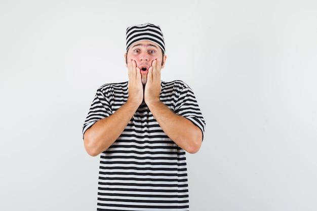 Giovane maschio che tiene le mani sulle guance in t-shirt, cappello e guardando agitato, vista frontale.